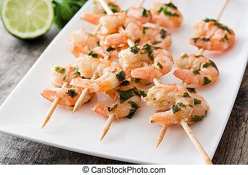 Shrimp skewers on wooden table