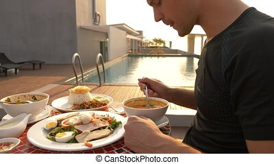 Shrimp soup is a Thai dish with a sour and spicy taste. the man is eating Tom Yam at a table by the pool. slow motion, close-up. concept of tourism tourism
