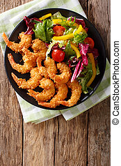 Shrimp tempura and salad of fresh vegetables close-up on a ...
