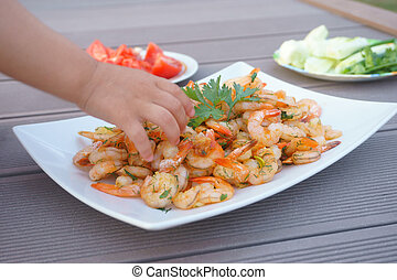 shrimps, children's hands take shrimps from the plate