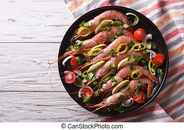 shrimps with herbs and vegetables in a pan. horizontal top view