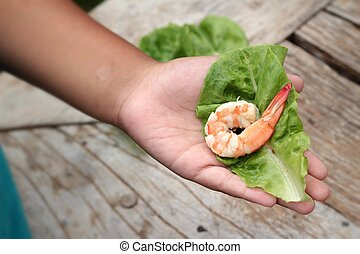 Shrimps with vegetables green leaves on hand