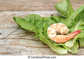 Shrimps with vegetables green leaves on wood background.
