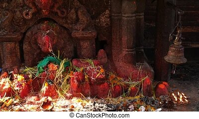 Shrine with sculpture and candles burning. Hindu temple shrine outdoors with sculpture of Ganesha and burning candles in sunlight, Nepal.