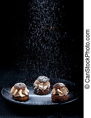 Shu cake sprinkled with powdered sugar on a black background