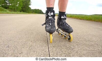 Shuffle inline skating on way in pine forest. Mans legs roller skating on the asphalt in hot summer day. Close up view to quick shuffle movement of four wheels inline boots.
