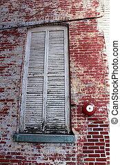 Shuttered windows in brick wall