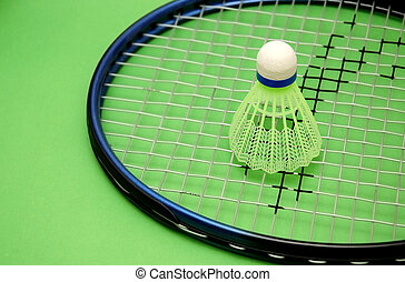 Shuttlecock and racket on green background