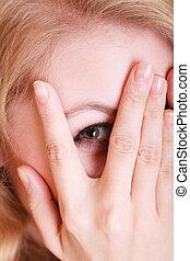 Shy afraid woman peeking through her fingers