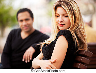 Shy Attractive Woman - A man and woman sitting on a bench,...