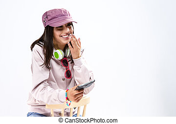 Shy Caucasian Brunette Girl With Smartphone and a Pair of Big Headphones. Against White Background