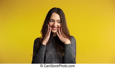 Shy coquette woman flirting and posing on yellow background....