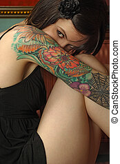 Shy female with tattoo - Photo of a shy young female with...
