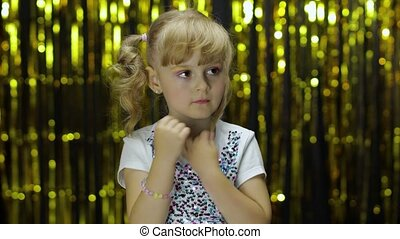 Shy girl is ashamed. Looking around. Little cute blonde kid teen teenager girl 4-5 years old in shiny white t-shirt posing isolated on foil fringe golden curtain background in studio. People emotions