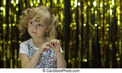 Shy girl is ashamed. She waves her hand. Little fun blonde kid teen girl 4-5 years old in shiny white t-shirt posing isolated on foil fringe golden curtain background in studio. . People emotions