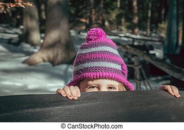 Shy girl peeking - Cute young caucasian girl peeking from...