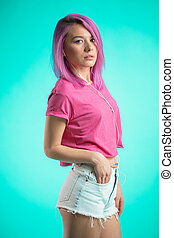 Shy lady with pink hair posing over blue background listening music in headphones.