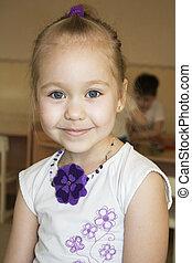 Modest, shy little girl in a kindergarten smille.