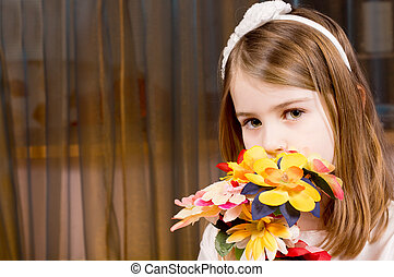 Shy little girl with a bouquet of flowers