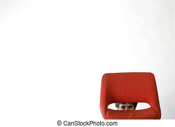 Shy Man - Shy man hiding behind a red chair.