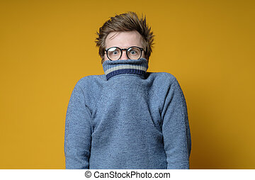 Shy, scared Caucasian shaggy man hiding behind his knitted sweater and looks uncertainly at the camera, on a yellow background.