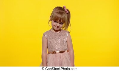 Shy shamed child girl, 5-6 years old in dress posing looking camera and smiling. Little kid feels guilty. Isolated on yellow background studio. People emotions. Copy space. 6k downscale. Slow motion