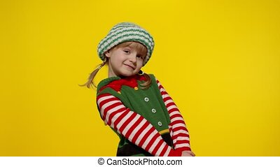 Shy shamed child girl in Christmas elf Santa helper costume posing looking camera smiling. Little kid feels guilty. Isolated on yellow background studio. People emotions. New Year holidays celebration
