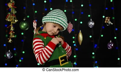 Shy shamed child girl in Christmas elf Santa helper costume posing and smiling. Little kid feels guilty. Isolated on black background with garland. People emotions. New Year holidays celebration
