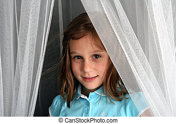 Shy - Young girl looking out from behind netting or curtains