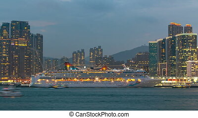 Shyline panorama timelapse day to night with towers and cruise liner in West Kowloon, Hong Kong.