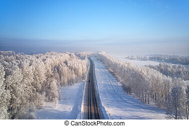 Siberian rural asphalt road under the snow. Siberian rural winter landscape with birch trees covered with hoarfrost. Aerial shot from drone