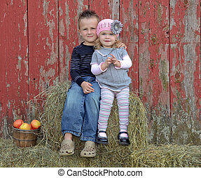 Sibling Love - Brother and sister on a country hay bale by...