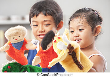 Sibling playing hand puppets, which were handmade