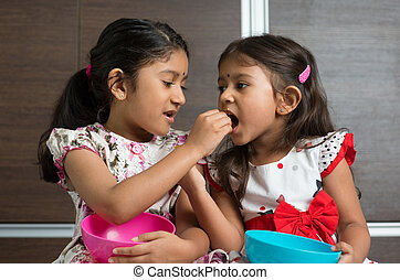 Sibling sharing food - Indian girls sharing food, murukku...