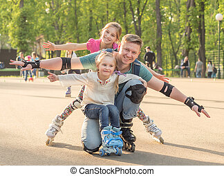 sisters and their father posing and roller skating