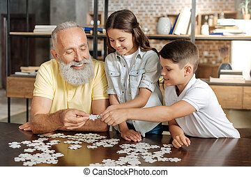 Siblings and their grandfather assembling a jigsaw puzzle
