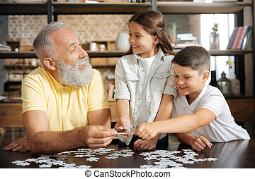 Siblings and their grandfather having fun while doing puzzle