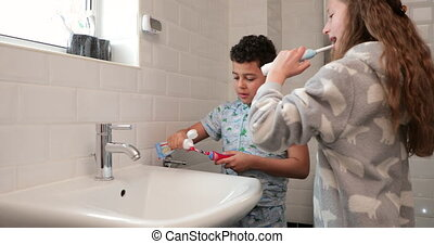 Siblings Brushing Their Teeth - Siblings are brushing their...