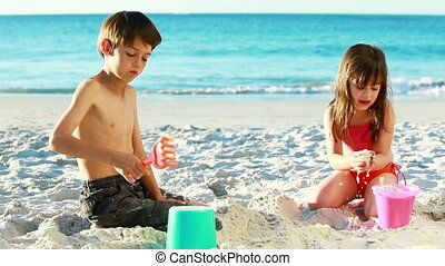 Siblings building sand castles on the beach