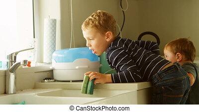 Siblings cleaning kitchen sink 4k - Siblings cleaning...
