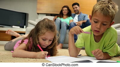 Siblings colouring on the floor while their parents are...