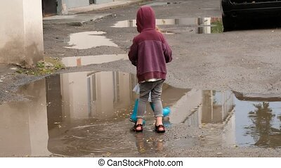 Full body brother and sister holding hands and spinning around while dancing near puddles of water on city street