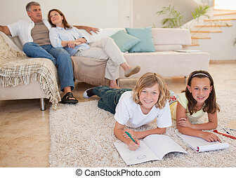 Siblings doing homework on the carpet with parents behind them