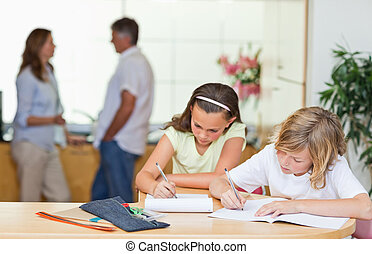 Siblings doing homework with parents behind them