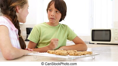 Siblings eating hot cookies from the cooling rack at home in...
