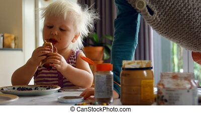 Siblings eating pancakes on dining table 4k - Front view of ...