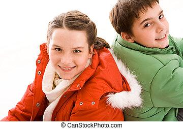 Siblings - Happy teenaged guy and girl looking at camera