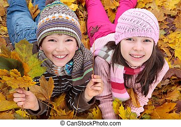 Siblings in fallen leaves - Smiling brother and sister...