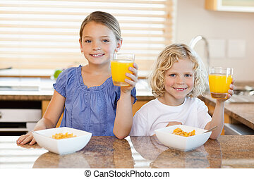 Siblings in the kitchen rising their glasses of orange juice