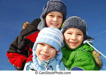 Three caucasian white kids in warm winter clothes smiling outdoors